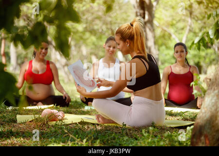 Pregnant women taking prenatal lesson in park. Teacher explaining baby growth inside belly with pictures and drawings.