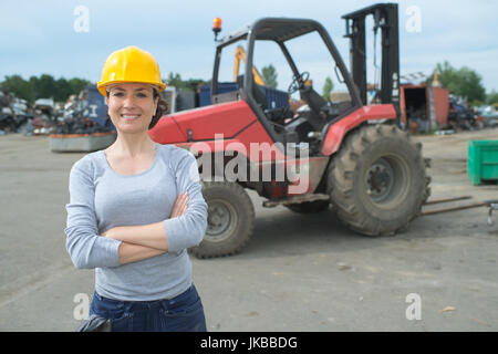 portrait of female fork lift truck driver in junk yard - Stock Photo