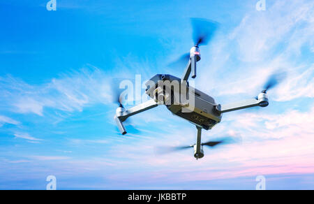 Drone in Flight over a blue sky background - Stock Photo