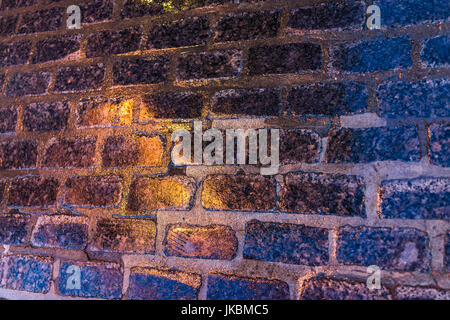 Macro closeup of colorful, vibrant and cobblestone street at night after rain with reflection of lights - Stock Photo