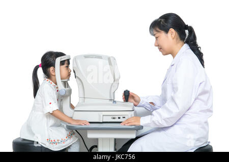 Asian Little Chinese Girl Doing Eyes Examination Through Auto refractometer in isolated White Background - Stock Photo