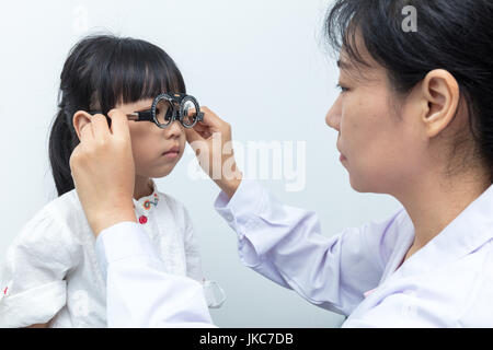Asian Little Chinese Girl Doing Eyes Examination by ophthalmologist in isolated White Background - Stock Photo