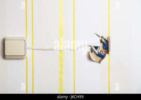 White light switch with a protruding wire on a white wall in yellow stripes - Stock Photo