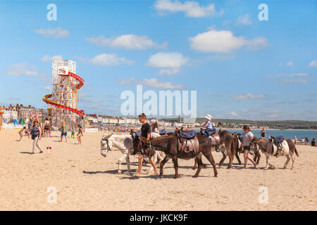 2 July 2017: Weymouth, Dorset, England, UK - Donkey rides on the beach at Weymouth, Dorset, England, UK. - Stock Photo