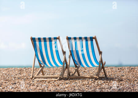 Two empty blue and white striped deck chairs facing out to sea, on a pebble beach.