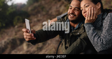 Horizontal shot of loving young couple on hike taking a self portrait with smartphone outdoors. Relaxed hiker couple - Stock Photo