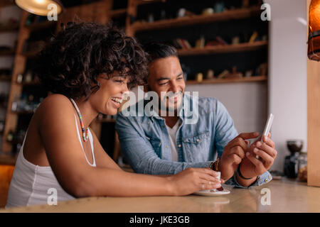 Young happy couple sitting at table in cafe and looking at mobile phone and smiling. African woman and caucasian - Stock Photo