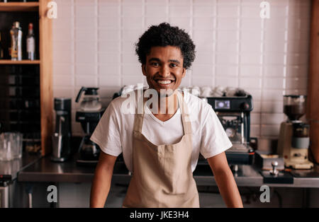Portrait of happy young barista standing at cafe counter. African man in apron looking at camera and smiling. - Stock Photo