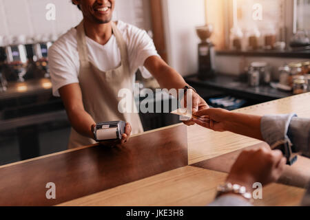 Cropped shot of customer giving credit card to male barista at cafe checkout counter. Customer paying through credit - Stock Photo
