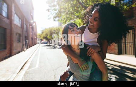 Outdoor shot of young woman carrying her female friend on her back. Two young woman having fun on city street. - Stock Photo