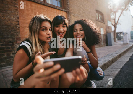 Female friends sitting outdoors and making selfie with smart phone. Multi ethnic group of women hanging out in the - Stock Photo