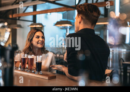 Young couple at bar with different craft beers on a wooden table. Man and woman talking at the bar counter.