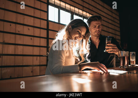 Young couple at the bar tasting different varieties of craft beers. Beautiful young woman with her boyfriend at - Stock Photo