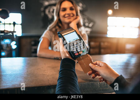 Cropped image of man paying using a credit card at bar with female behind the counter. Cashless payment at the bar. - Stock Photo