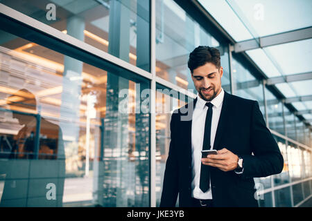 Businessman using smartphone and smiling at airport. Young business executive with mobile phone at airport. - Stock Photo