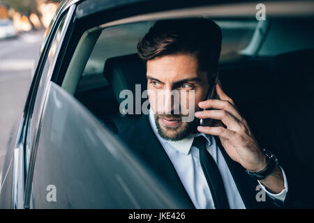 Businessman talking on the mobile phone and looking outside the window while sitting on back seat of a taxi. Male - Stock Photo