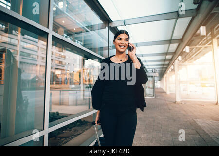 Happy young woman on business trip walking with luggage and talking on cellphone at airport. Travelling businesswoman - Stock Photo