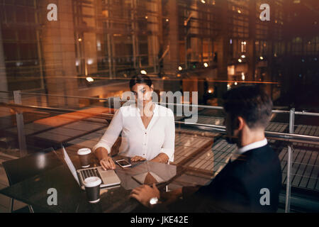 Businesswoman sitting at cafe table with man discussing business. Business people waiting at airport lounge with - Stock Photo