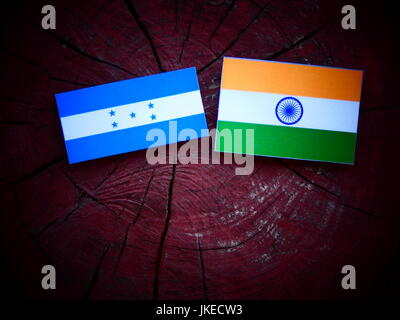 Honduran flag with Indian flag on a tree stump isolated - Stock Photo