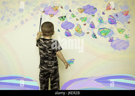 Concept of creativity child. The little boy draws on the wall. Butterflies and clouds. Photo illustration for your - Stock Photo