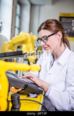 Woman using device in factory with industrial robots - Stock Photo