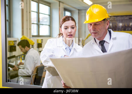 Two engineers in factory looking at plan - Stock Photo