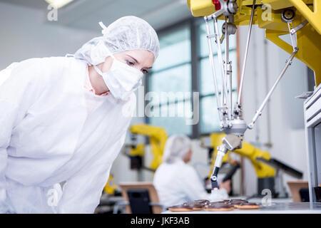 Woman in factory examining robot handling cookies - Stock Photo