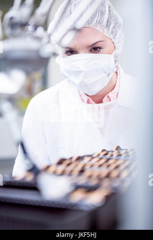 Woman in factory looking at robot handling cookies - Stock Photo