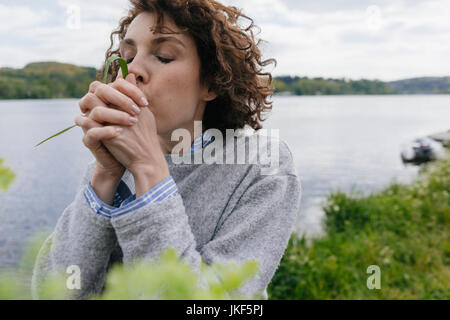 Woman at lake blowing grass blade - Stock Photo