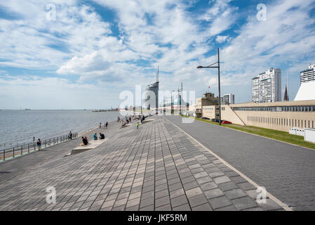Germany, Bremerhaven, waterfront promenade with Atlantic Hotel Sail City in background - Stock Photo
