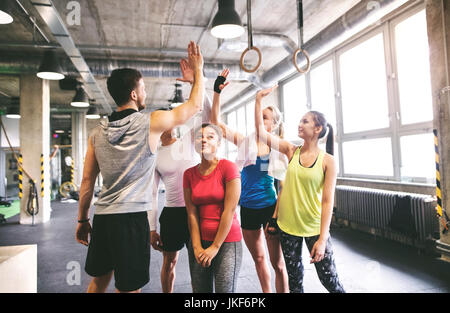 Group of young people high fiving in gym - Stock Photo