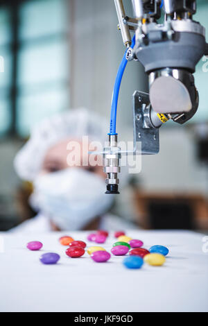 Robot handling sweets with woman in background - Stock Photo