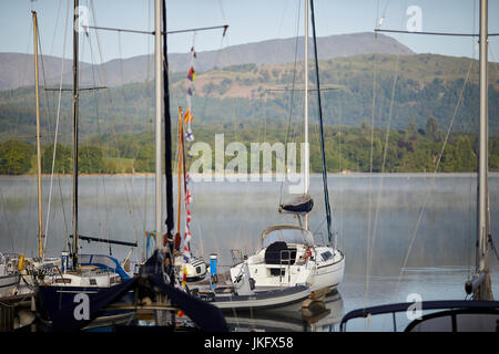 Morning mist over Windermere a large lake in Cumbria's Lake District National Park, soared boats at Low Wood Marina, - Stock Photo