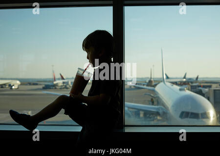 New York City,  United States,  JFK Airport Virgin  a small young boy passenger resting as the drinks looking out - Stock Photo