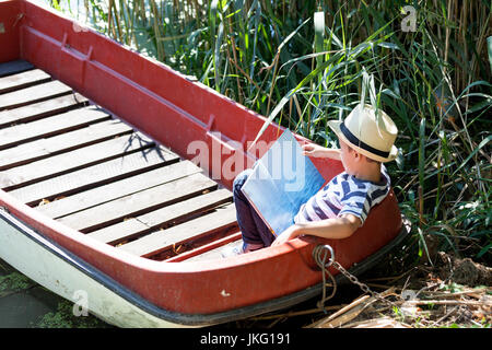 Little cute little boy with a hat is sitting in a boat by the river and reading his favorite book. He loves nature - Stock Photo