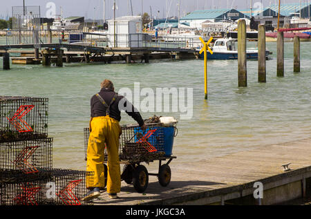 A crew member pushes a buggy along a floating pontoon at the harbour at Warsash in Hampshire as he helps unload - Stock Photo