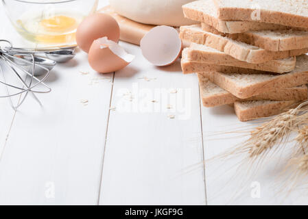 slice bread with ingredients for making bread on with wood background, copy space - Stock Photo