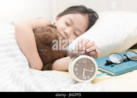 cute little hand girl reaching to turn off alarm clock on the bed in the morning - Stock Photo