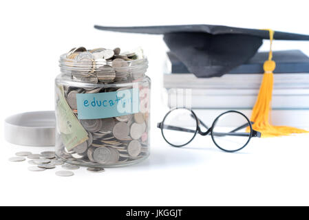 education budget concept. education money savings in a glass jar with glasses, graduate hat and book isolated on - Stock Photo