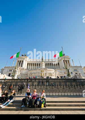 Vertical perspective view of people sitting on the steps at the Vittoriano or Victor Emanuele II monument in Rome. - Stock Photo