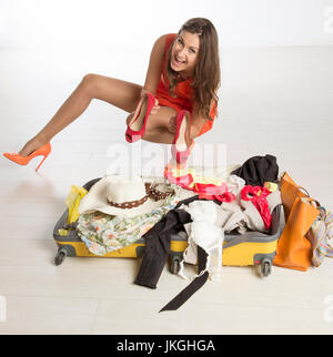 Holidaymaker packing a suitcase, summer clothing and a large hat - Stock Photo