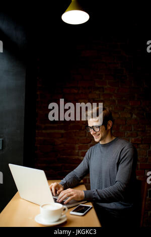 Portrait of a young man using laptop in the coffee shop - Stock Photo
