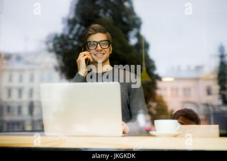man siting in the window of a coffee shop and speaking on the phone - Stock Photo