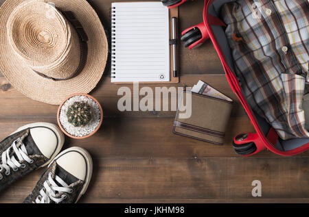 Travel preparations on wooden table, hat wallet, bag, notebook and shirt - Stock Photo