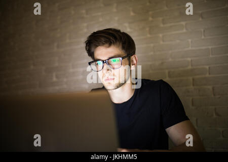 Closeup view of bearded young businessman in eyeglasses working at office at night man using laptop - Stock Photo