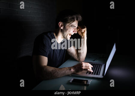 Young man working on computer at night in dark office the designer works in the later time. Hacker - Stock Photo