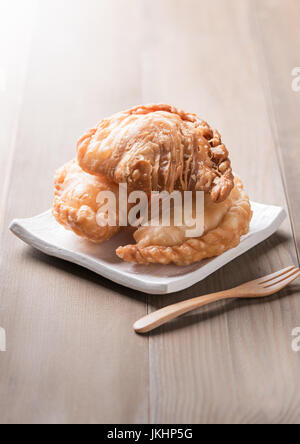 Curry puff pastry on wood background - Stock Photo