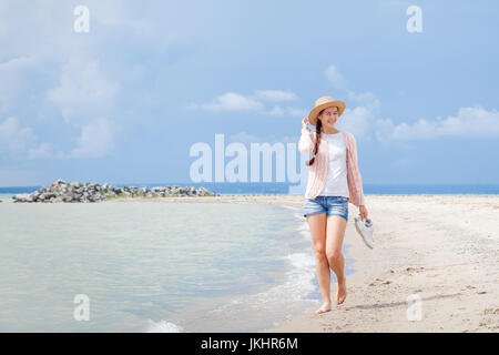 A young woman in a white T-shirt, denim shorts and a pink knitted cardigan holds a straw hat and walks next to the - Stock Photo
