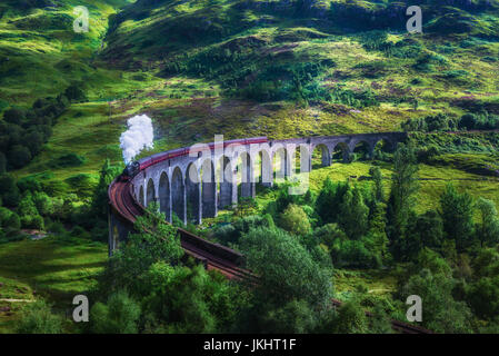 Glenfinnan Railway Viaduct in Scotland with the Jacobite steam train passing over. Artistic vintage style processing. - Stock Photo
