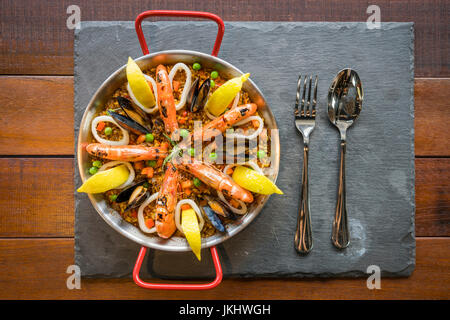 Paella with seafood vegetables and saffron served in the traditional pan top view. - Stock Photo
